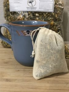 One serving of tum tea in it's reusable tea bag by a mug